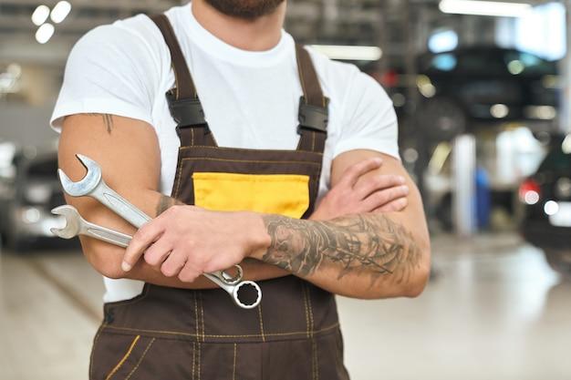 Męski mechanik z mięśni rękami i kluczem do utrzymywania tatuażu