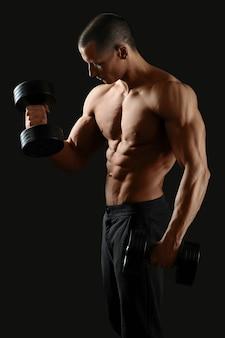 Męski mężczyzna bez koszuli pompujący żelazo, pokazujący swoje seksowne, podarte ciało