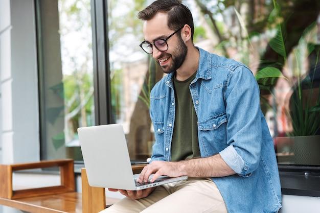 Męski młody mężczyzna noszący okulary, piszący na laptopie podczas pracy w kawiarni miejskiej na świeżym powietrzu
