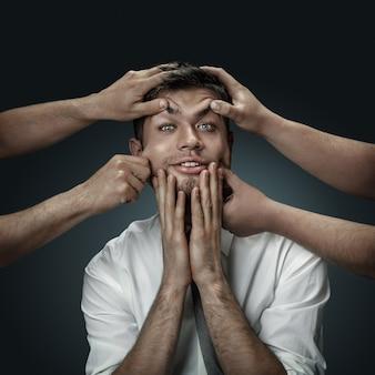 Męski model otoczony rękami, jak jego własne myśli na ciemnej ścianie