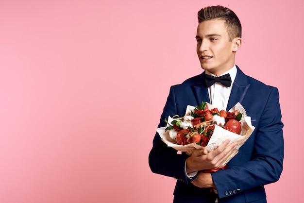 Męski model pozujący w klasycznym garniturze z bukietem kwiatów
