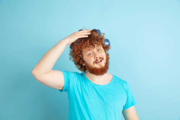 Męski model z naturalnymi rudymi włosami robiący swoją fryzurę, potrzebuje bardziej kręconych