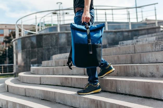 Męski model z plecakami podróżuje na letnie wakacje do miasta
