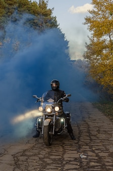 Męski motocyklista w hełmie na rowerze w pięknym jesień przodzie
