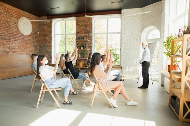 Męski mówca prezentujący prezentację w sali na uniwersyteckiej publiczności warsztatowej lub sali konferencyjnej