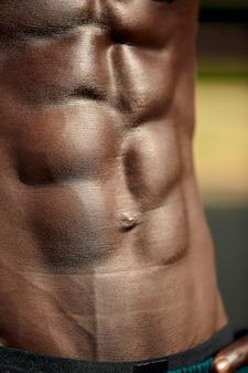 Męski muskularny brzuch, zbliżenie, ulga w brzuchu czarnego mężczyzny.