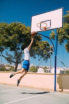 Męski nastoletni uczeń robi koszykówka skoku strzałowi