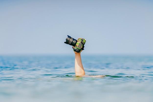 Męski nurek pływa pod wodą i utrzymuje photocamera przy jego ręką nad woda w oceanie. zabawne i niebezpieczne hobby i praca.