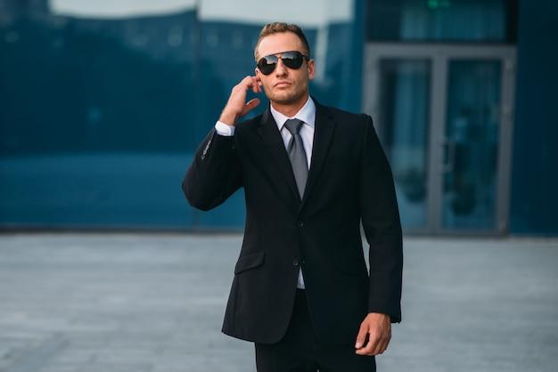 Męski ochroniarz używa słuchawek zabezpieczających na zewnątrz, profesjonalnych narzędzi komunikacyjnych.