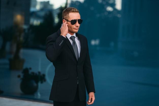 Męski ochroniarz używa słuchawek zabezpieczających na zewnątrz
