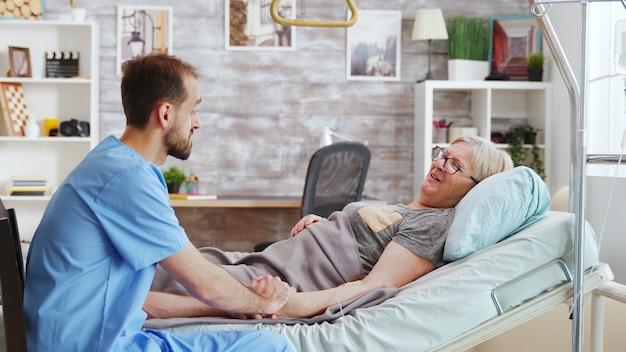 Męski opiekun rozmawiający z chorą starszą panią leżącą w szpitalnym łóżku, bierze kobietę za rękę