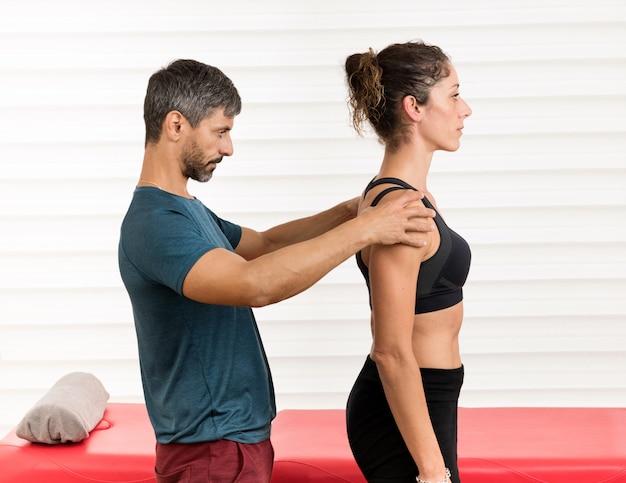 Męski osteopata dokonuje oceny postawy