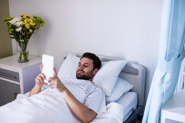 Męski pacjent używa cyfrową pastylkę w oddziale
