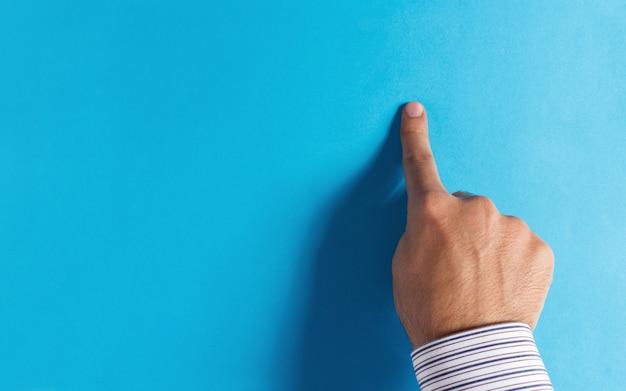 Męski palec wskazujący na niebieskim tle