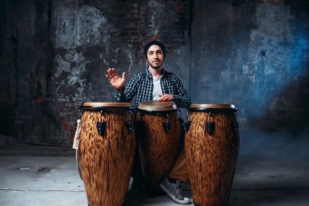 Męski perkusista grający na drewnianych bębnach bongo w sklepie fabrycznym