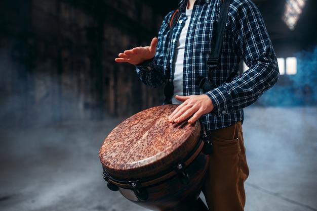 Męski perkusista grający na drewnianym bębnie