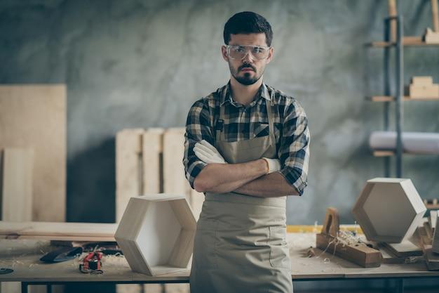 Męski pewny siebie robotnik budowniczy stanąć w domu garaż w domu krzyż ręce gotowe naprawy przywrócić wszystkie meble odzież warsztatowa w kratę koszula w kratę