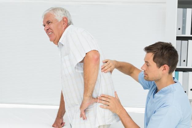 Męski physiotherapist egzamininuje senior obsługuje z powrotem