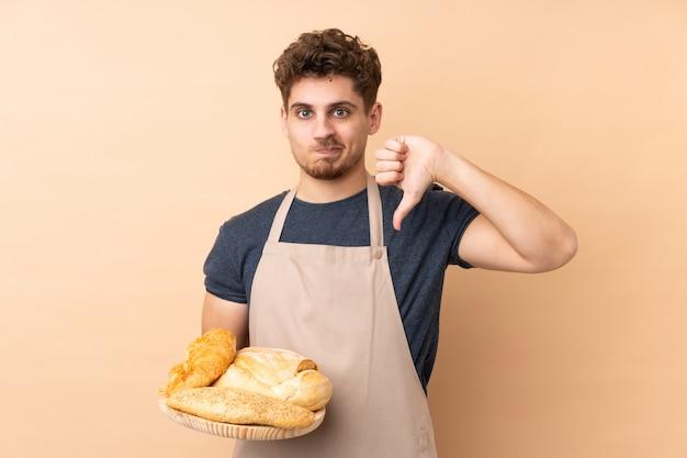 Męski piekarz trzyma stół z kilka chlebami na beż ścianie pokazuje kciuka puszka znaka