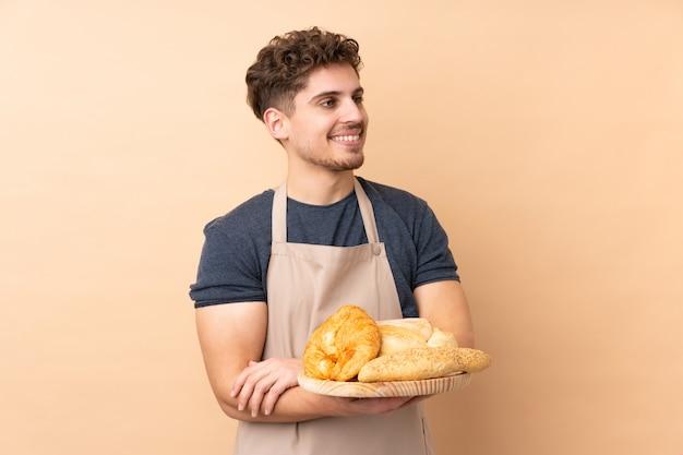 Męski piekarz trzyma stół z kilka chlebami odizolowywającymi na beż ścianie izoluje patrzeć strona
