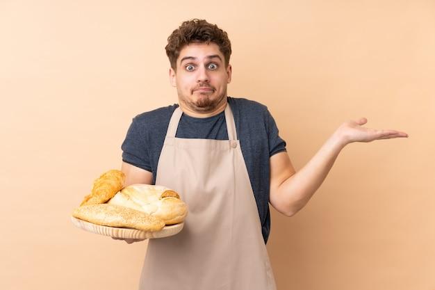 Męski piekarz trzyma stół z kilka chlebami odizolowywającymi na beż ścianie ma wątpliwości z zmieszanym wyrazem twarzy