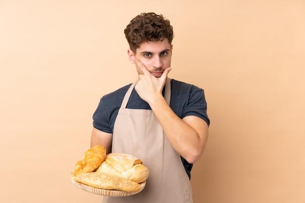 Męski piekarz trzyma stół z kilka chlebami odizolowywającymi na beż ścianie myśleć główkowanie pomysł