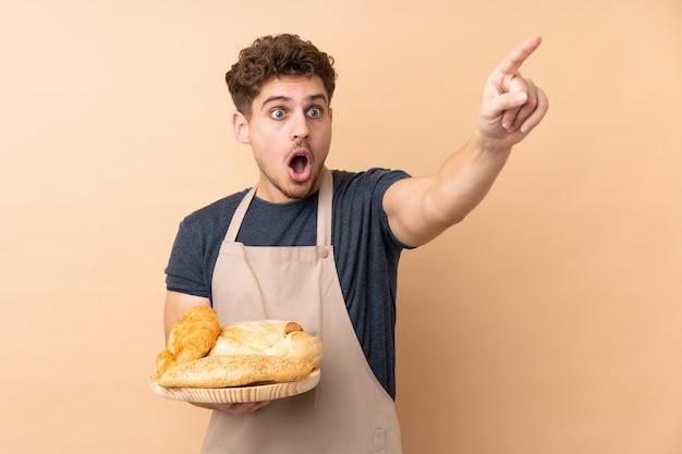Męski piekarz trzyma stół z kilka chlebami odizolowywającymi na beż ścianie wskazuje daleko od
