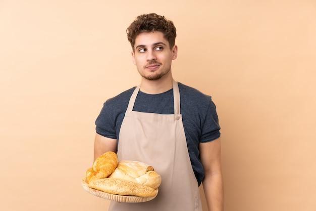 Męski piekarz trzyma stół z kilka chlebami odizolowywającymi na beżowej ściennej pozyci i patrzeje strona