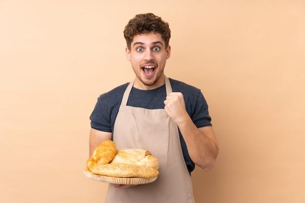 Męski piekarz trzyma stół z kilkoma chlebami na beżowej ścianie świętuje zwycięstwo