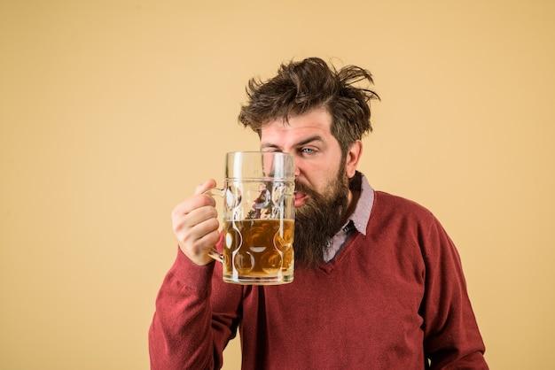 Męski piwowar trzyma szklankę z piwem oktober fest degustację świeżo warzonego piwa piwowar trzyma szklankę z