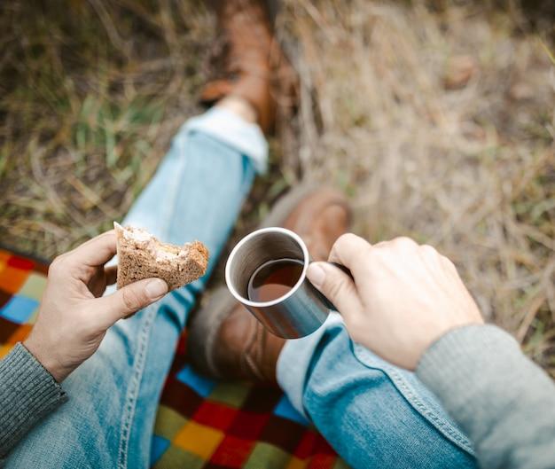 Męski podróżnik je przekąskę i pije herbaty na trawie