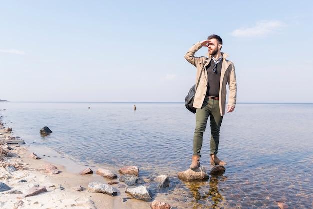 Męski podróżnik stoi blisko jeziora osłania jego oczy