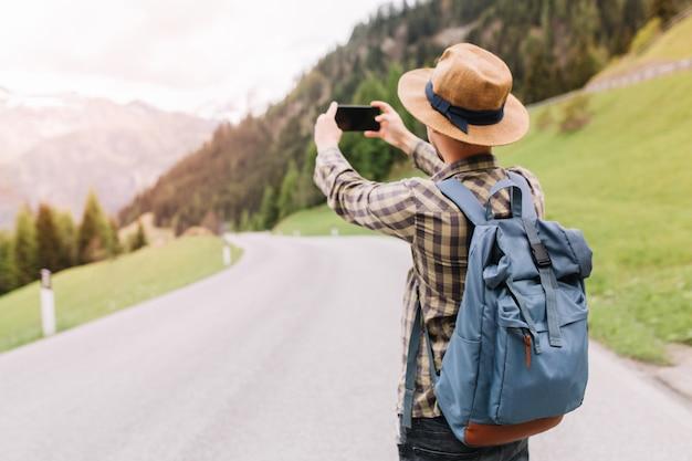 Męski podróżnik w modnej kraciastej koszuli robiącej zdjęcie niesamowitego krajobrazu z lasem i górami