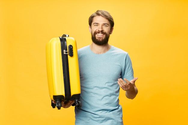 Męski podróżnik z walizką w jego rękach pozuje w studiu, wakacje