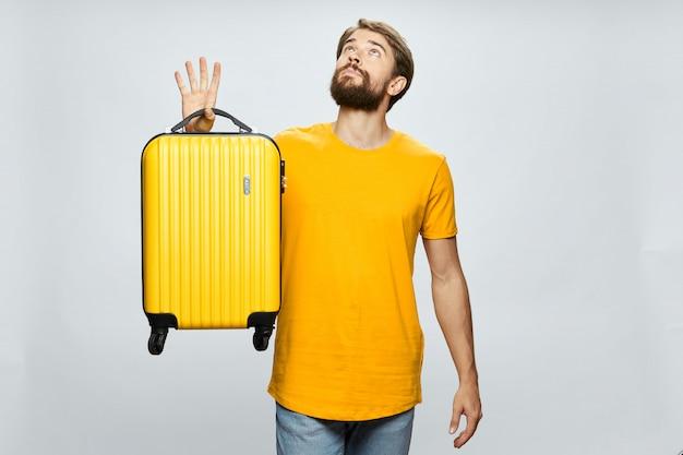Męski podróżnik z walizką w jego rękach pozuje w studiu
