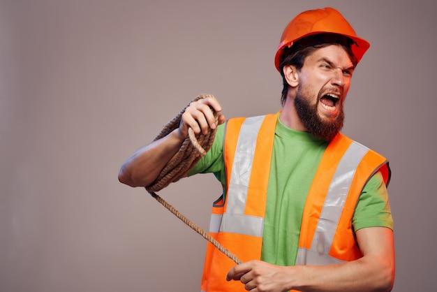 Męski pomarańczowy kask budowniczy na głowie profesjonalisty