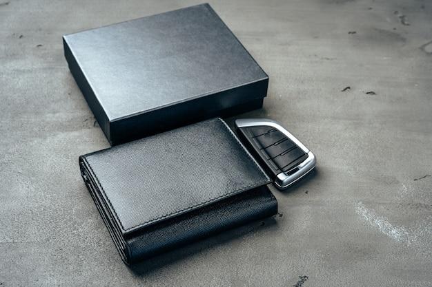 Męski portfel skórzany i kluczyk do samochodu na ciemnoszarym tle z bliska