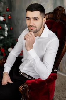 Męski portret. przystojny brunetki mężczyzna w białej koszula i klasycznych czarnych jeans pozach w popielatym studio sitt