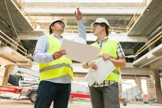 Męski pracownik budowlany i inżynier przy budową.