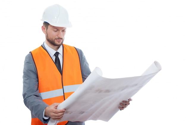 Męski pracownik budowlany jest ubranym ochronnego hełm i zbawczą kamizelkę egzamininuje budynek.