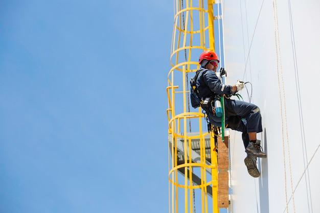 Męski pracownik w dół zbiornik ze zbiornikiem płyta ze sznurem drabina dostęp kontrola bezpieczeństwa grubości zbiornika magazynowego gaz propan.