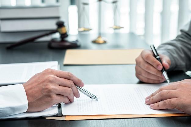 Męski prawnik omawiający sprawę prawną negocjacji ze spotkaniem z klientem z kontaktem z dokumentem w koncepcji sali sądowej, prawa i sprawiedliwości.