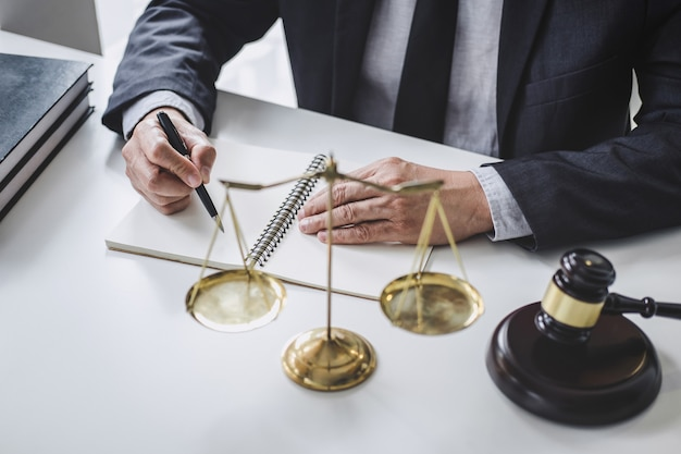 Męski prawnik pracuje z papierami, książkami prawa, drewnianym młotkiem i skalą na stole.