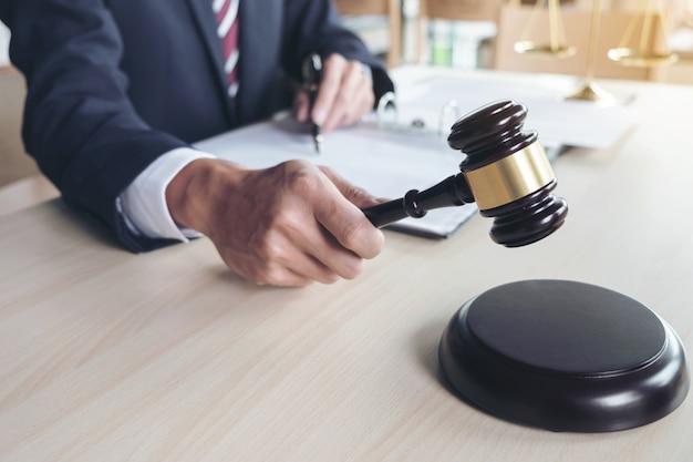 Męski prawnik pracuje z skala sprawiedliwość, książki, donosi skrzynkę na drewnianym stole