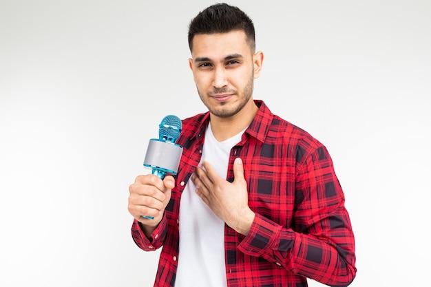 Męski prezenter z mikrofonem w rękach ma ból gardła na białym odosobnionym studiu