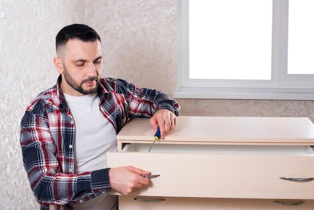 Męski producent mebli montuje meble w mieszkaniu