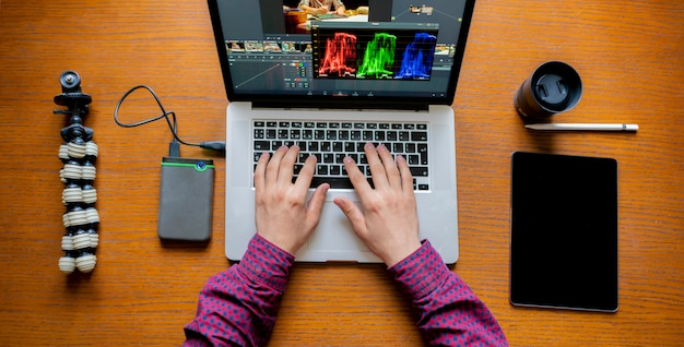 Męski producent redaguje wideo na jego laptopie w studiu