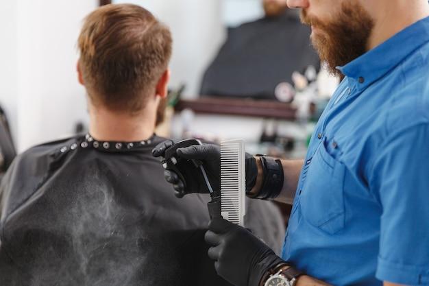 Męski profesjonalny fryzjer obsługujący i przygotowujący narzędzia