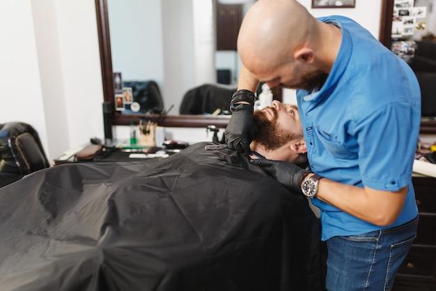 Męski profesjonalny fryzjer obsługujący klienta, golący grubą brzytwę z dużą brodą