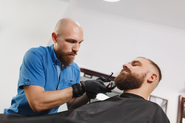 Męski profesjonalny fryzjer obsługujący klienta maszynką do strzyżenia